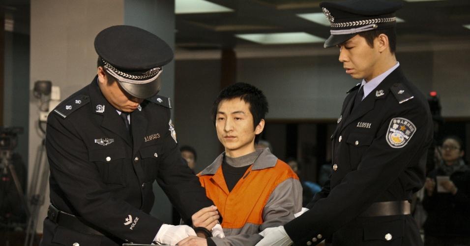 Agricultor chinês é escoltado por policiais em Pequim, na China, após ser condenado a 13 anos de prisão por roubar joias e obras de arte de palácio imperial na Cidade Proibida