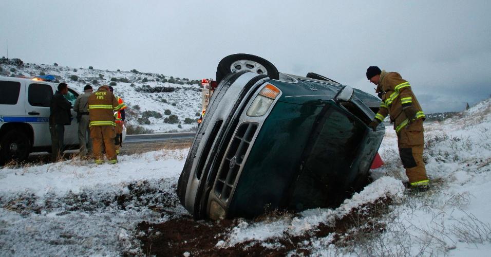 Bombeiro observa interior de carro que capotou em Yavapai County, no Arizona, nos Estados Unidos, após o motorista perder o controle da direção
