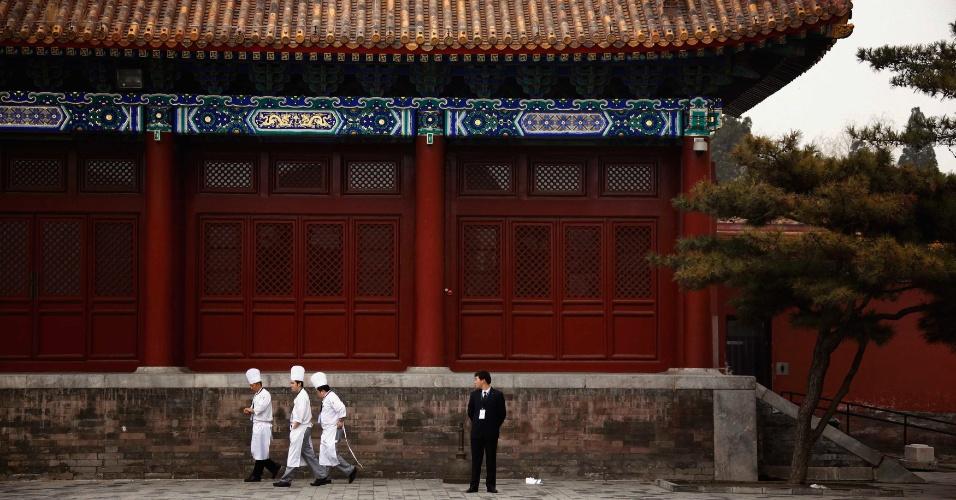 Segurança observa três cozinheiros caminharem durante evento de rede de hotéis na Cidade Proibida, em Pequim, na China