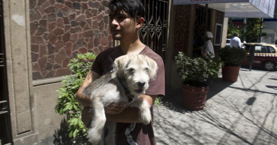 Jovem segura seu cachorro ao deixar sua casa na Cidade do México, após um forte terremoto que atingiu o sul do México