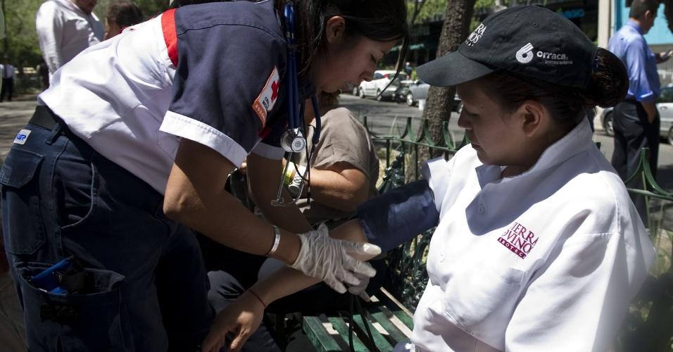 Membro da Cruz Vermelha ajuda uma mulher que passou mal nas ruas da Cidade do México, após um forte terremoto que atingiu o sul do México