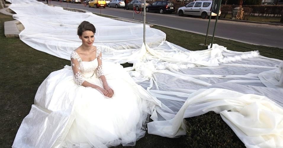 Modelo Emma Dumitrescu, 17, exibe vestido de noiva com a cauda mais longa do mundo na Romênia.