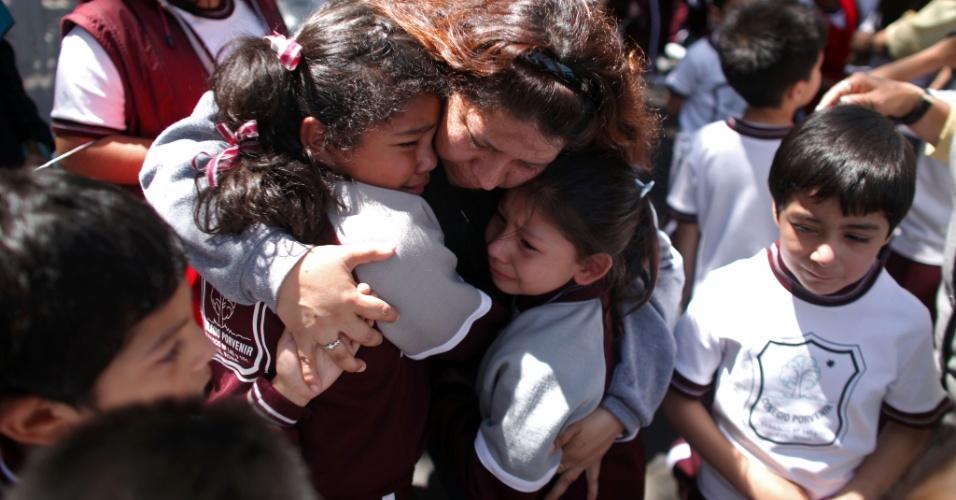 Mulher conforta seus filhos fora de uma escola no bairro de Roma, na Cidade do México, após um terremoto atingir o sul do México