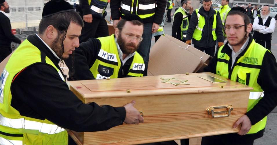 21.mar.2012 - Voluntários carregam os caixões de Rabbi Jonathan Sandler, 30, de seus filhos Arieh, 5, e Gabriel, 4, e da garota Miriam Monsonego, 7, para o funeral. Eles morreram durante tiroteio em escola judia de Toulouse, na França