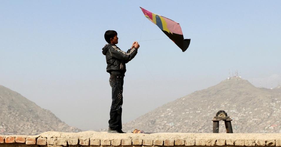 Jovem afegão segura pipa sobre teto de uma casa em Cabul, no Afeganistão