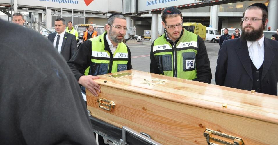 Voluntários carregam um dos caixões com vítimas de massacre em escolar francesa do avião para uma van no Aeroporto de Ben Gurion, em Tel Aviv, em Israel