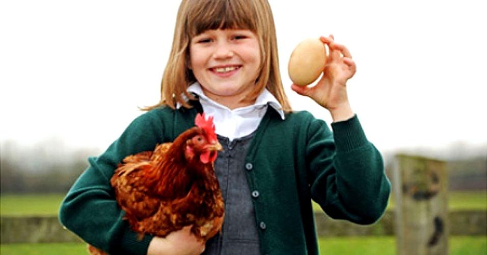 A garotinha Harriet Whitaker, 8, segura a galinha Popples, 2, e o superovo botado pelo animal. O ovo mede 12,7 cm de altura, tem 20,32 cm de circunferência e pesa 187,11 gramas