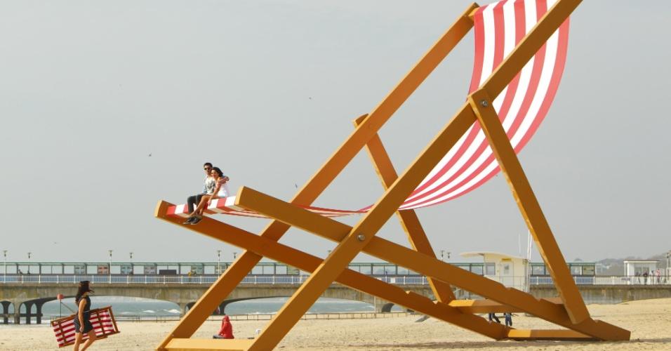 """Casal senta em cadeira gigante que pode ser confirmada pelo Livro dos Recordes como a maior cadeira de praia do mundo, na praia de Bournemouth, sul da Inglaterra (Reino Unido). A """"cadeirona"""" foi construída pelo artista Stuart Murdoch, pela quase seis toneladas e mede quase 8,5 metros de altura"""