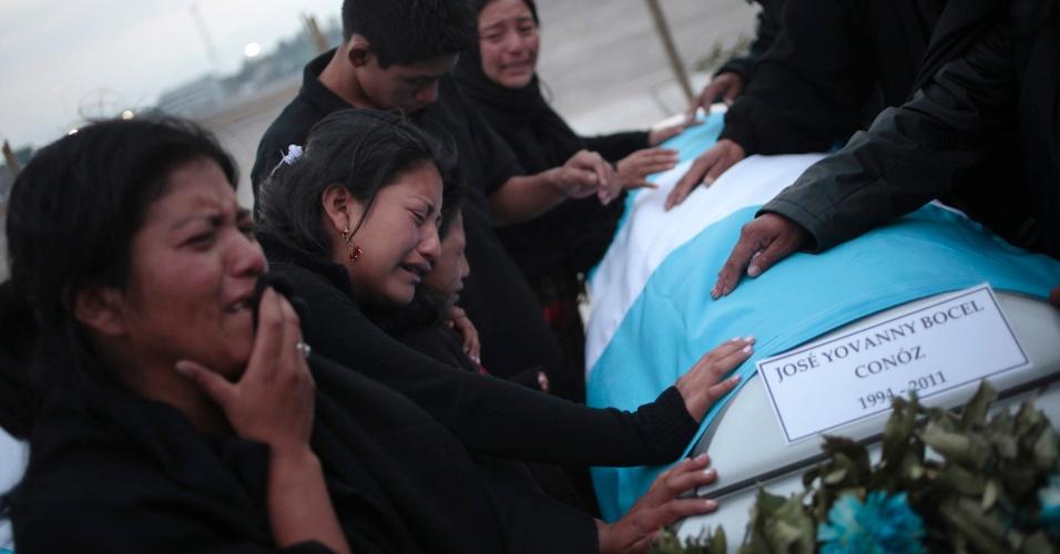 Familiares de imigrante guatemalteco que teve o corpo encontrado em vala comum na cidade de Tamaulipas, no México, choram sobre caixão em base aérea na Cidade da Guatemala