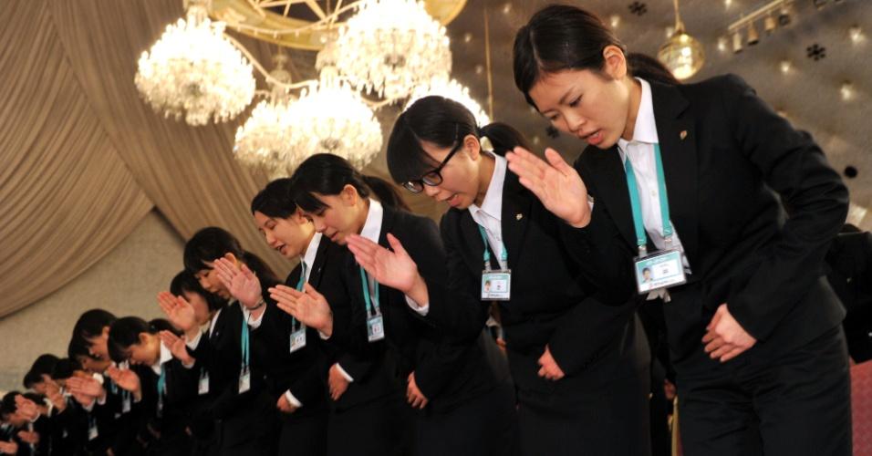 Funcionárias recém-contratadas da maior empresa de varejo do Japão, a Seven & I Holdings, aprendem a utilizar linguagem de sinais para deficientes auditivos em cerimônia anual de integração em Tóquio