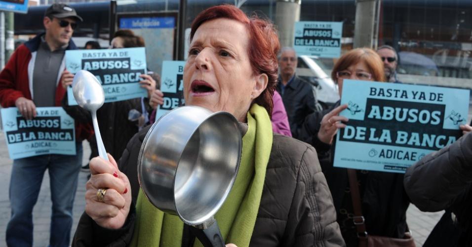 Mulher usa panela em protesto nesta quinta-feira (22) contra 'abusos dos bancos' em frente à sede de instituição financeira em Madri, na Espanha
