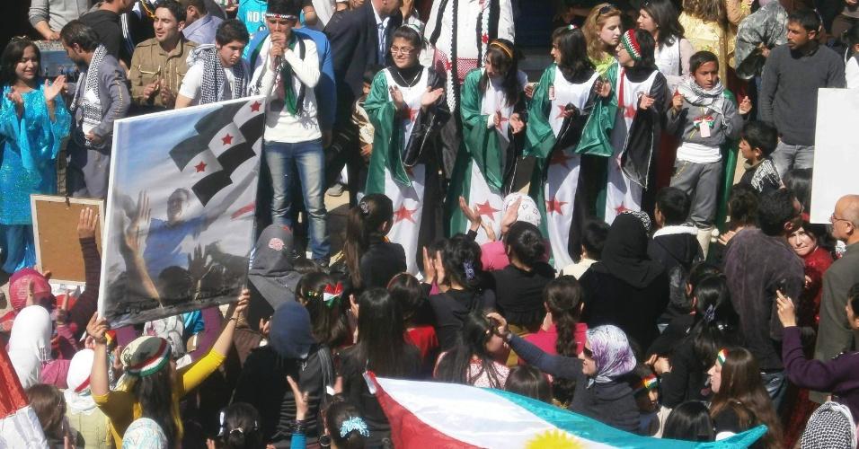 Opositores ao presidente sírio Bashar al Assad usam bandeira curda e ?vestem? bandeira independentista em protesto na cidade de Qamishli, na Síria