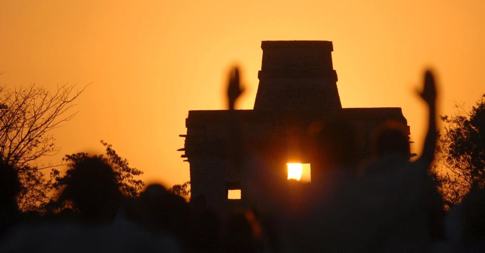 Pessoas levantam as mãos enquanto o sol brilha através de janela do Templo das Sete Bonecas na cidade maia de Dzibilchaltun, em Yucatán, no México