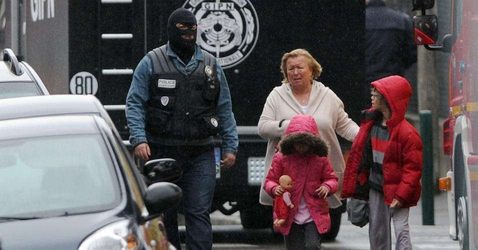 Policial de forças especiais de segurança acompanha mulher e crianças durante cerco a Mohamed Merah, em Toulouse, França