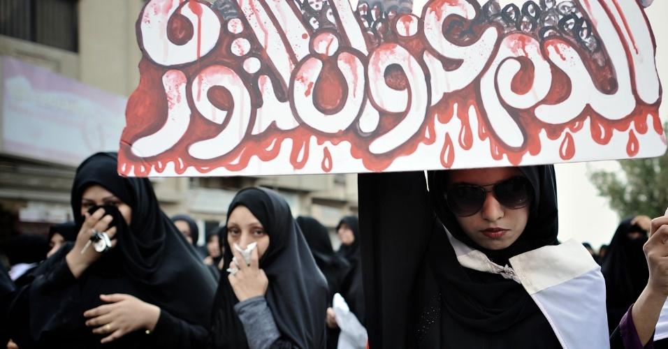cartaz em árabe levado por uma mulher bareinita na cidade de Jidhafs, a oeste de Manama milhares de pessoas tomaram as ruas de povoados xiitas próximos a capital, pedindo mudanças no regime político do Bahrein