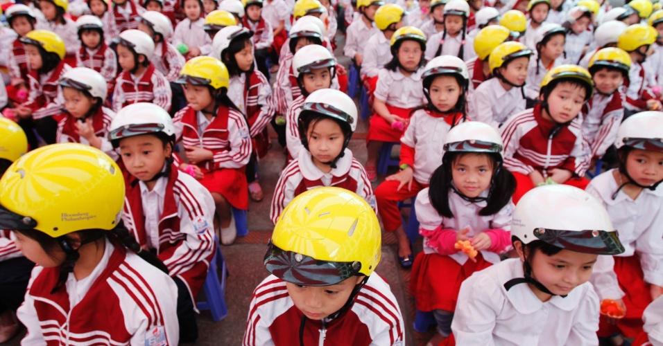 Crinças com capacetes aguardam a chegada do prefeito de Nova York, Michael Bloomberg, durante evento nesta sexta-feira (23) para ofertar capacetes para crianças usarem motocicletas em uma escola em Hanói, no Vietnã