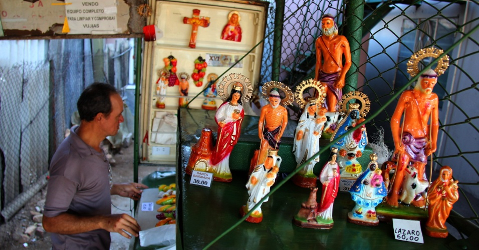 Em Havana, vendedor dispõe imagens religiosas antes da visita do Papa. Bento 16 chega a Cuba no próximo dia 26