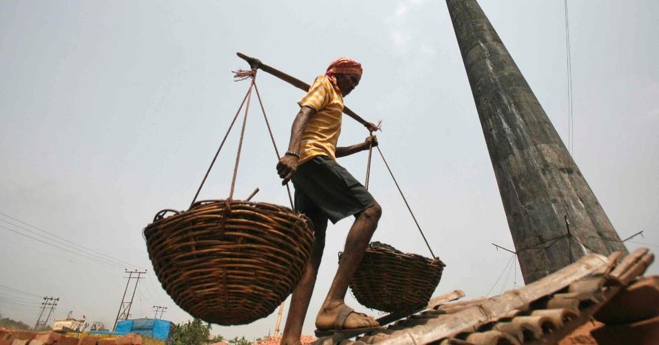 Homem carrega cestas com carvão nas proximidades de Agartala, na Índia
