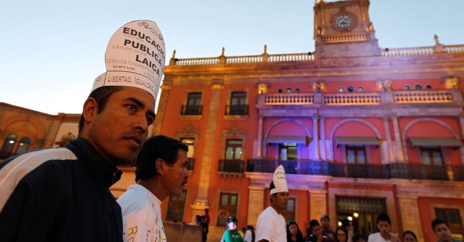 Homens usam mitras (cobertura de cabeça e insígnia pontificial utilizada pelo papa) para protestar contra a visita de Bento 16, no centro de Leon, no estado mexicano de Guanajuato. O pontífice chega ao México nesta sexta-feira (23) para uma visita de três dias