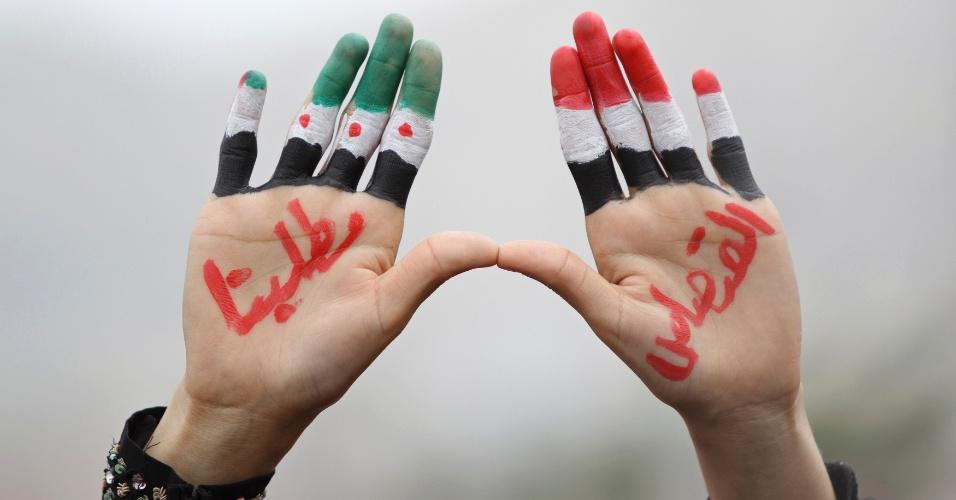 Jovem mostra mãos pintadas com as cores da bandeira iemenita (à dir.) e do movimento de oposição ao governo sírio (à esq.) durante protesto, em Sanaa, capital do Iêmen