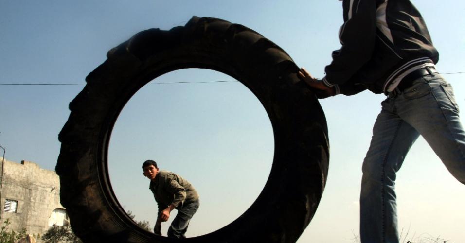 Jovem palestino move pneu enquanto outro se prepara para arremessar uma pedra contra soldados israelenses durante protesto em Kfar Kadum, na Cisjordânia