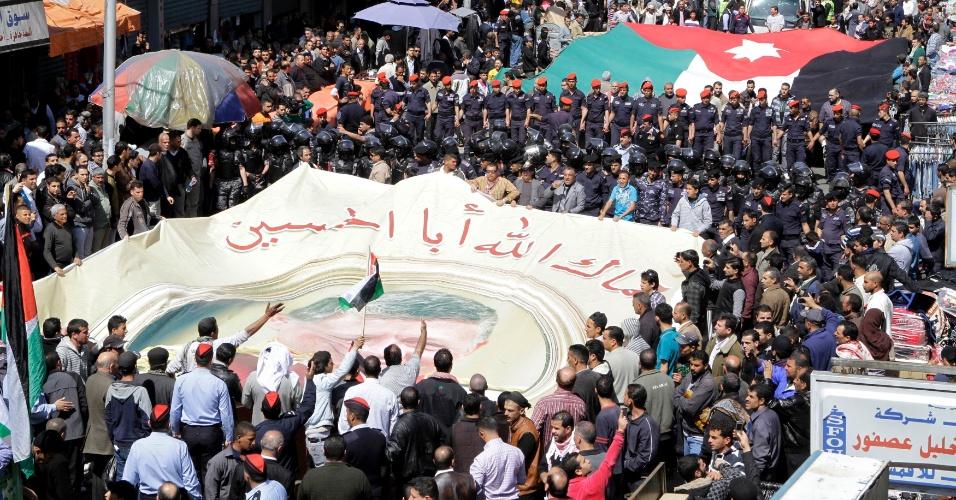 Partidários do governo da Jordânia seguram bandeira com imagem do rei Abdullah 2º em Amã, capital do país