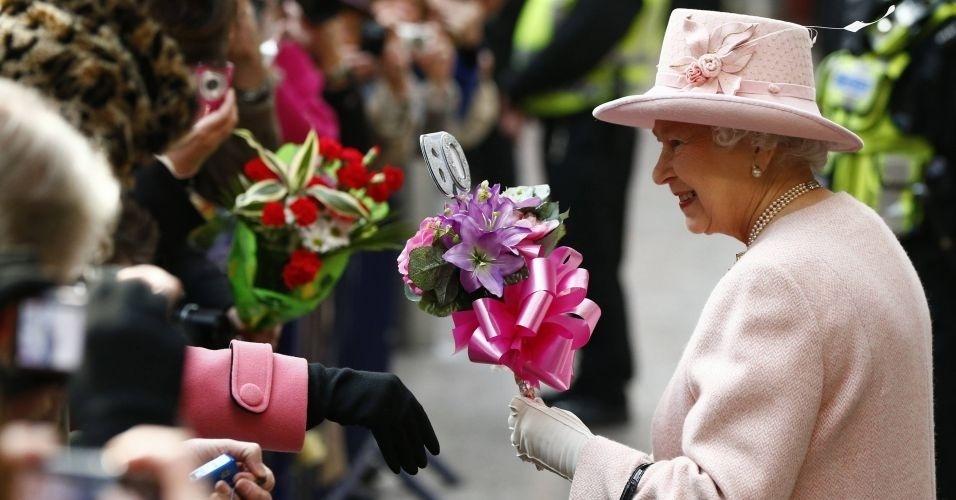 Rainha Elizabeth recebe flores ao desembarcar na estação Victoria em Manchester, norte da Inglaterra