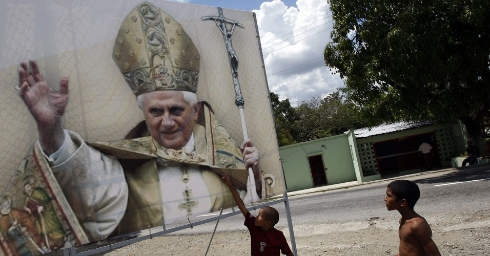 Crianças observam cartaz com imagem do Papa Bento 16, neste sábado, em Cuba. O pontífice chegará ao país na próxima segunda-feira (25)