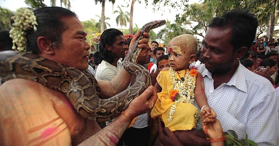 Devoto usa cobra para abençoar criança durante festival hindu em Yangon, cidade localizada em Mianmar