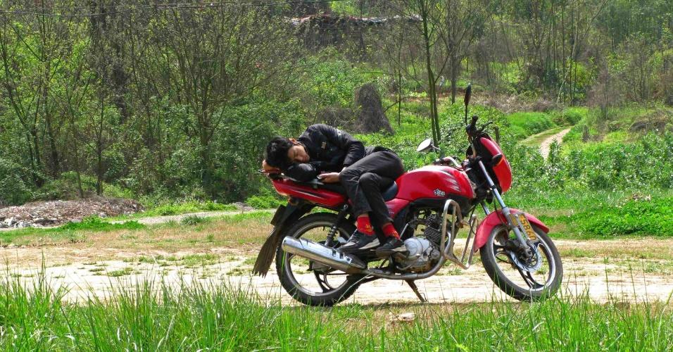 Homem tira uma soneca em cima de sua moto estacionada próxima a uma rodovia de Suining, na província de Sichuan, na China