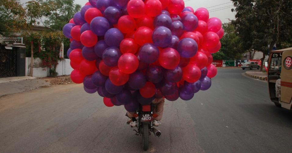 Homem transporta balões em uma moto na cidade de Lahore, no Paquistão