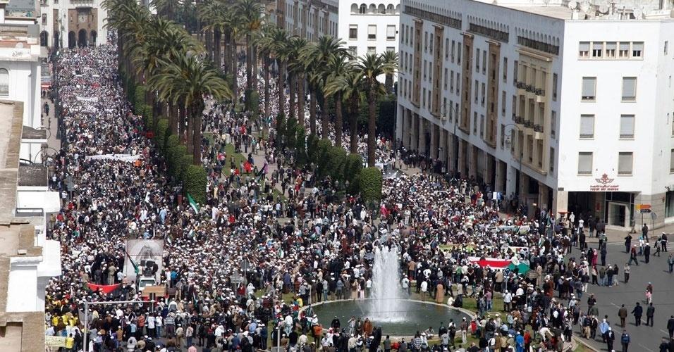Marroquinos seguram bandeiras e cartazes em frente ao parlamento durante protesto realizado neste domingo (25) contra a participação da delegação israelense na 8ª sessão da Assembleia Parlamentar Euro-Mediterrânica