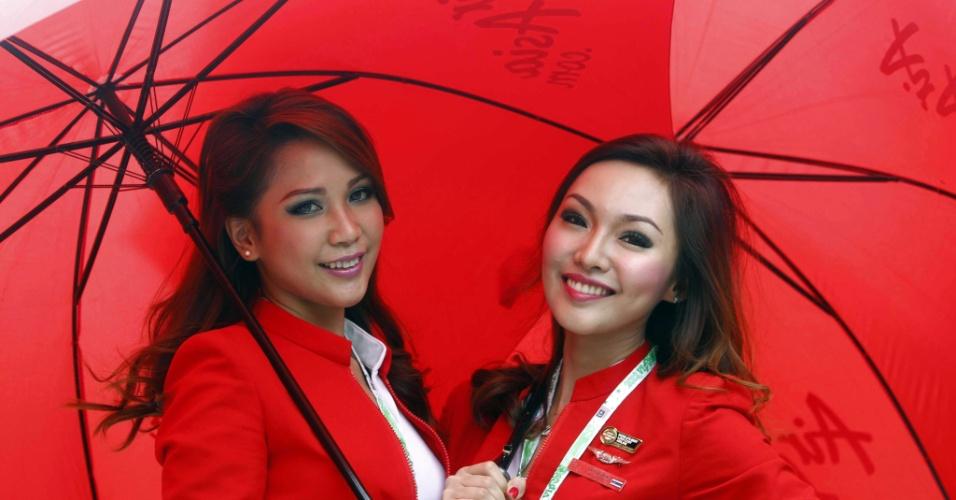 Modelos posam com guarda-chuvas no circuito de Seopang, neste domingo (25), durante o Grande Prêmio da Malásia de Fórmula 1, em Kuala Lumpur