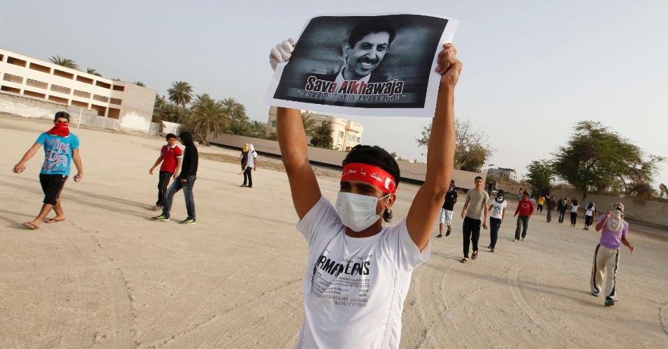 Bareinita segura  cartaz com foto de Abdulhadi al-Khawaja, condenado à prisão perpétua por seu envolvimento nas revoltas pró-democracia, durante protesto realizado em Budaiya, a oeste de Manama