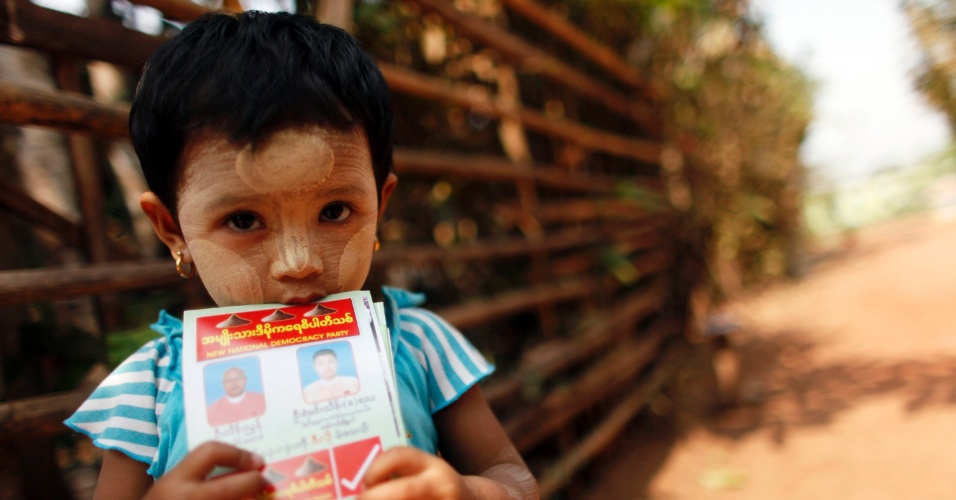 Criança segura panfleto do Partido da Nova Democracia Nacional durante comício em Mayangone Township, em Mianmar