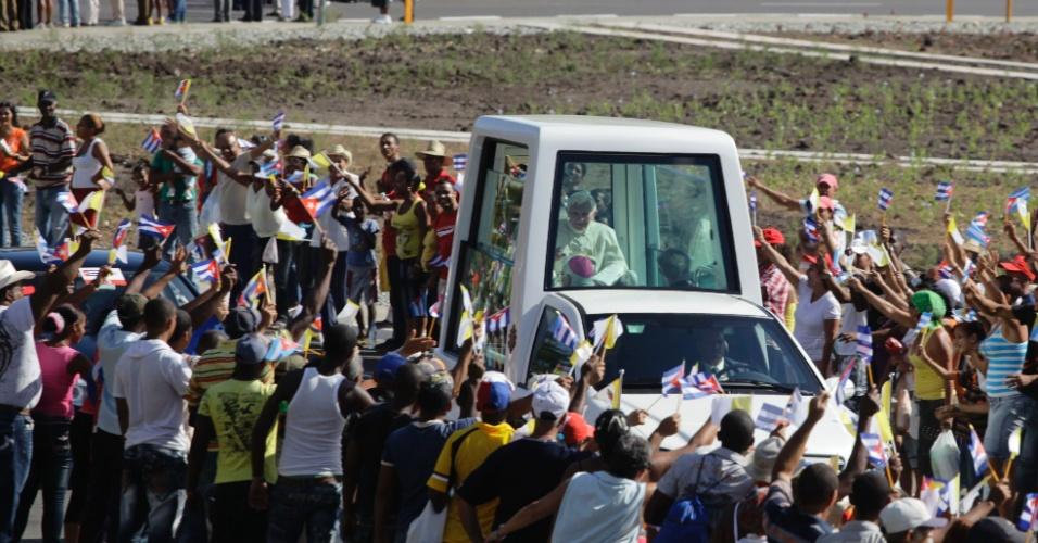 Cubanos se aglomeraram pelas ruas de Santiago de Cuba nesta segunda-feira (26) para ver o papa Bento 16 passar com seu papamóvel, logo após desembarcar no país para uma visita de três dias na esperança de impulsionar o diálogo da Igreja Católica com o regime comunista