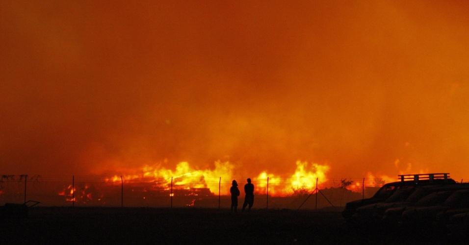 Duas pessoas observam incêndio em um dos terminais internacionais do porto de Thilawa, 25 km ao sul de Yangun, em Mianmar