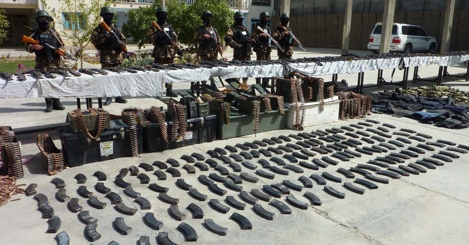 Forças afegãs de segurança fazem guarda em Candahar, no Afeganistão, diante de parte dos 200 fuzis, 17 toneladas de explosivos e munições apreendidos de insurgentes