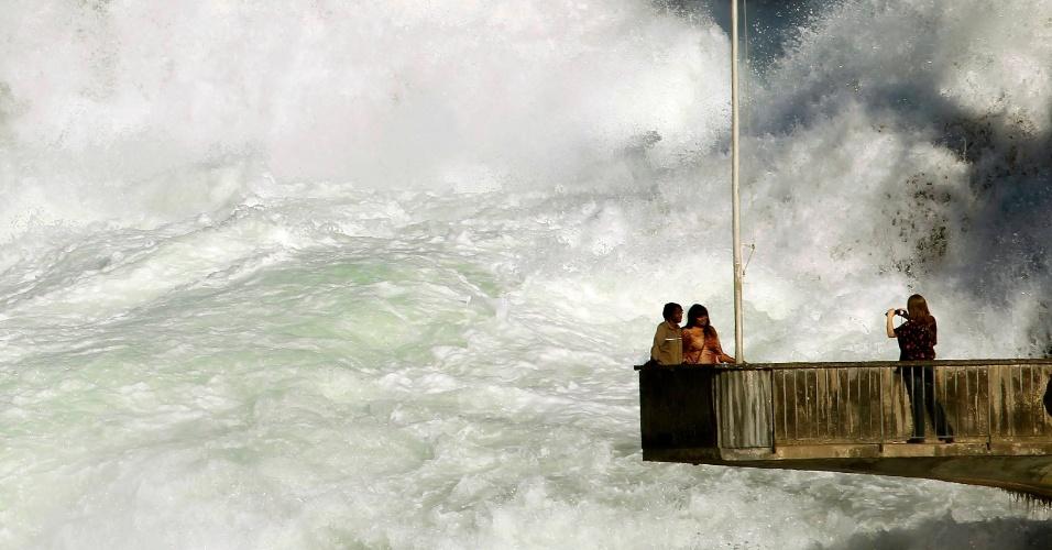 Mulher tira foto de casal nas quedas de Rhine, perto da cidade de Schaffhausen, no norte da Suíça