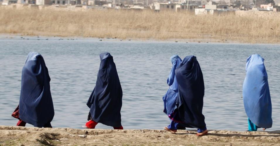 Mulheres caminham à beira de lago em Cabul, no Afeganistão