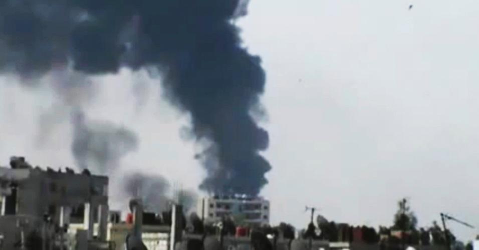 Reprodução de imagem de TV, transmitida pela rede de notícias Shaam News, mostra fumaça em edifício de Homs, na Síria