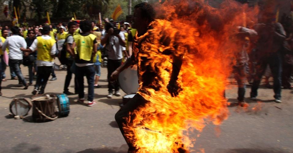 Tibetano exilado corre após atear fogo em si mesmo, em Nova Déli, durante protesto contra a visita do presidente da China, Hu Jintao, à Índia
