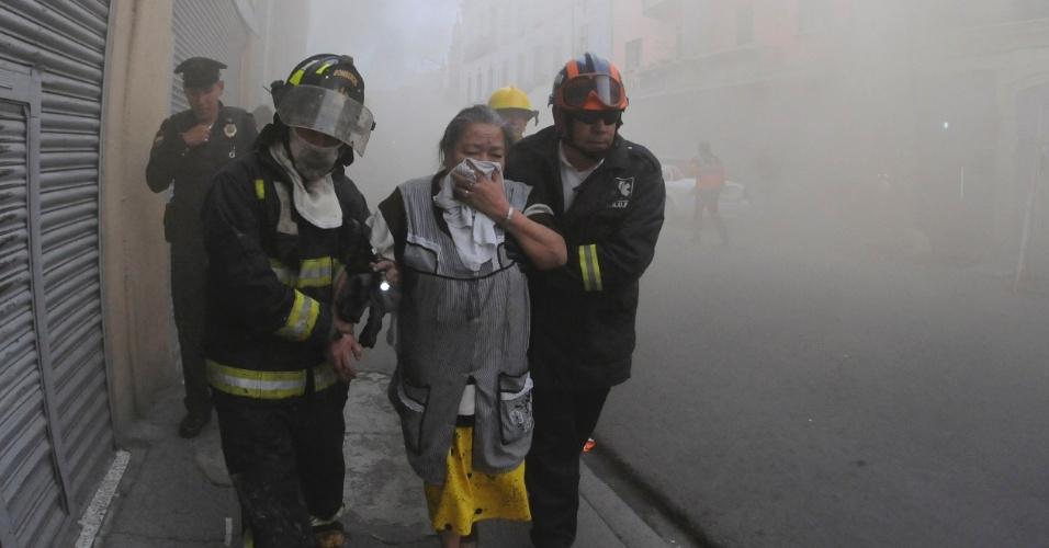 Bombeiros auxiliam vendedora durante evacuação de armazém no centro da Cidade do México