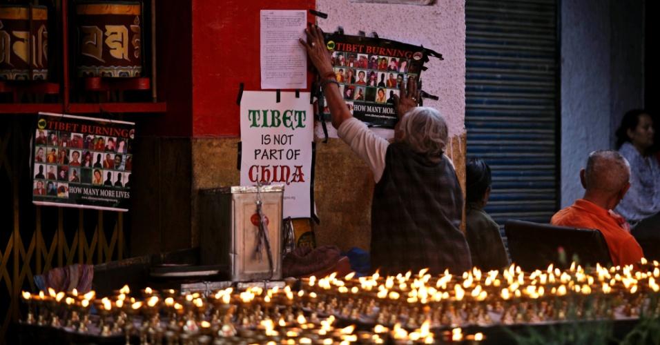 Exilado tibetano cola na parede de templo cartaz de tibetanos que se autoimolaram, em Nova Déli, na Índia