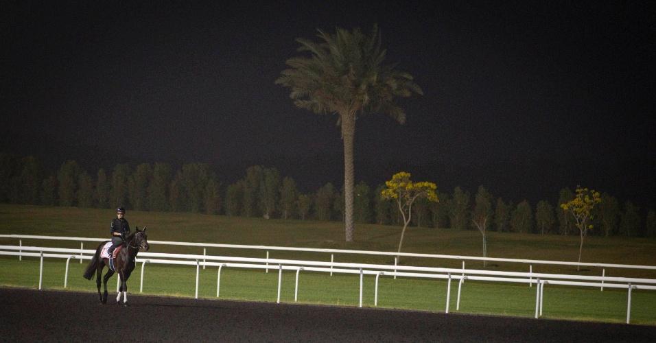 Jockey passeia durante o amanhecer em preparação para o a 17ª Copa do Mundo de corrida de cavalos, na pista Meydan em Dubai,