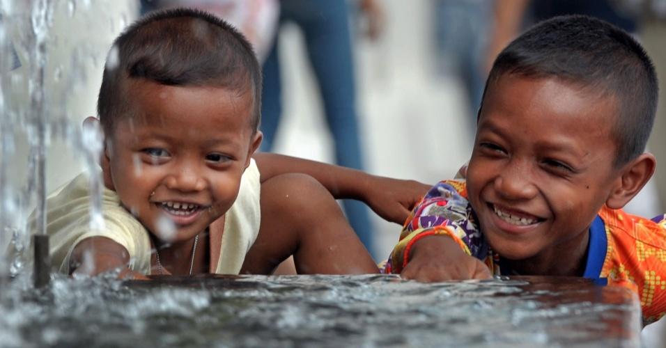 Meninos brincam em fonte de água durante a estação quente em Bancoc, na Tailândia