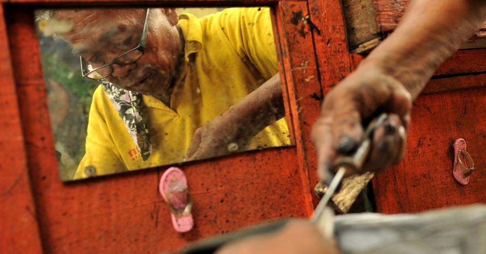 Sapateiro Rodolfo Arpon, 66, trabalha em avenida de Manila, nas Filipinas