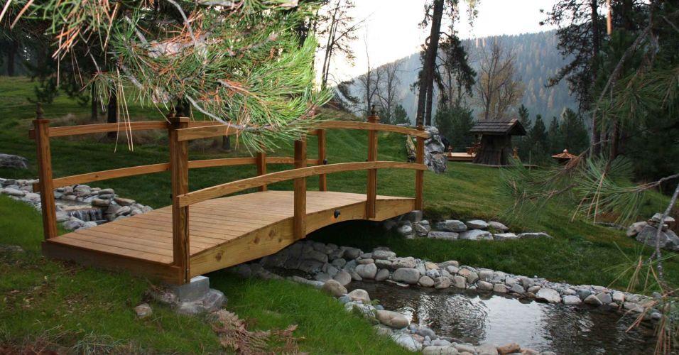 Uma ponte e um rio com pedras brancas dão o tom e o clima de
