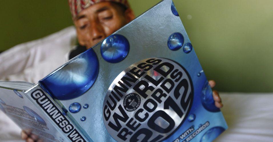 O nepalês Chandra Bahadur Dangi, 72, folheia seu exemplar do livro dos recordes