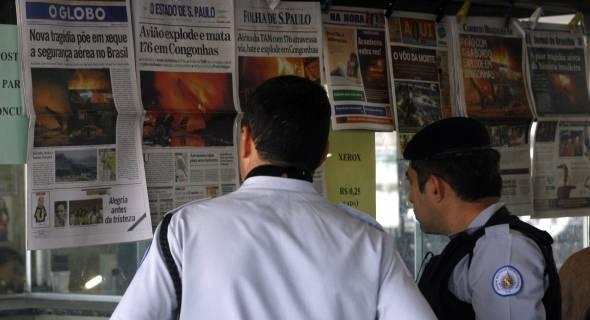 18.jul.07 - Policiais observam as notícias do acidente nas proximidades de Congonhas